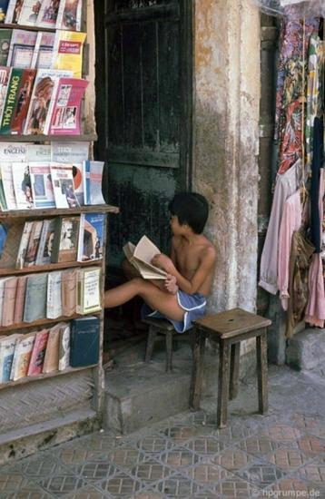 Cậu bé đọc sách trong một cửa hàng sách cũ ở phố cổ.