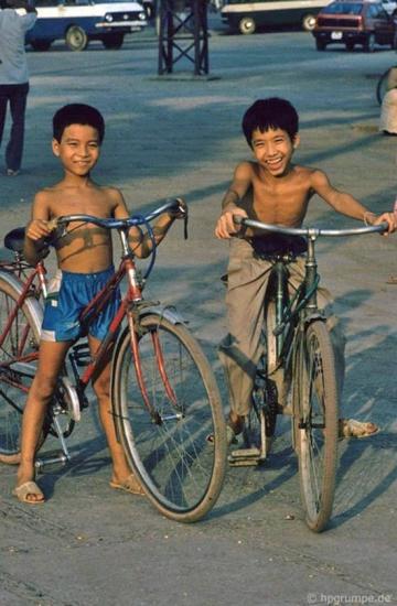 Hai cậu bé tập đi xe đạp trên phố.