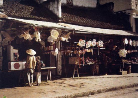 006 Phố Hàng Gai, Tết Trung thu 1915. Một phần con phố hồi cuối thế kỷ 19 có tên là phố Hàng Tiện: có những cửa hàng nhỏ, thợ vừa tiện vừa bán những đồ thờ, mâm bồng, đèn nến, ống hương, đài rượu, khuôn ván, mõ gỗ… Họ tiện cả những thứ nói trên nhưng cỡ nhỏ bé để trẻ con chơi.