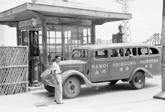 """Hà Nội 1940. Trạm xăng Texaco gần cầu Long Biên. Thời gian đầu do cầu Long Biên còn hẹp chưa được mở rộng hai bên nên xe chở khách đi tỉnh không thể qua cầu, phải đi phà sang bên kia sông. Năm 1923, việc mở rộng đường hai bên cầu hoàn thành nên xe không phải qua phà nữa. Ba hãng xăng là Shell, Socony và Texaco (của Mỹ) mở điểm bán xăng và Texaco đã giành được quyền tài trợ xây nhà bán vé khang trang, trên nóc nhà bán vé có cột hình vuông 4 mặt có tên Texaco. Theo tạp chí """"Tự nhiên"""" xuất bản bằng tiếng Pháp năm 1926 phát hành tại Hà Nội thì năm 1925, trung bình một ngày có 4 xe tải, 166 xe ô tô con và 79 lượt xe buýt qua lại cầu Long Biên. Ảnh: Harrison Forman"""