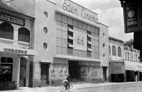 """Hà Nội 1940. Bên ngoài rạp Eden. Cái rạp này hồi trước tên là """"Cinema Palace"""", là rạp phim hoành tráng nhất ở Hà Nội. Nó có mặt tiền thật đẹp tựa cái vỏ con sò cách điệu. Thời thực dân Pháp tạm chiếm Hà Nội (1947-1954), rạp đổi tên thành """"Eden"""". Người chủ mới không biết muốn tỏ ra khác trước hay vì trào lưu kiến trúc tân kỳ mà che cái mặt tiền đẹp đó bằng những tấm gỗ dán vuông thành sắc cạnh như trong ảnh này để đến nỗi mọi người quên bẵng diện mạo kiến trúc ban đầu, ngay cả khi sau này nó được đổi thành rạp chiếu bóng """"Công nhân"""" rồi sàn diễn chuyên nghiệp của Đoàn kịch nói Hà Nội. Ảnh: Harrison Forman"""