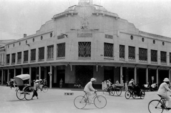 Cuối thế kỷ 19, các cửa hàng bách hóa (Grands Magasins, Department Stores) ở Paris xuất hiện rất thành công dẫn đến điều tất yếu là mô hình này được lan rộng ở Việt Nam với Maison Godard, sau này thành Grands Magasins Réunis (sau này là Bách Hóa Tràng Tiền và bây giờ là Tràng Tiền Plaza) xây khoảng 1900. Ở Sài Gòn, Grands Magasins Charner tức Thương xá Tax xây năm 1921. Ảnh: Harrison Forman