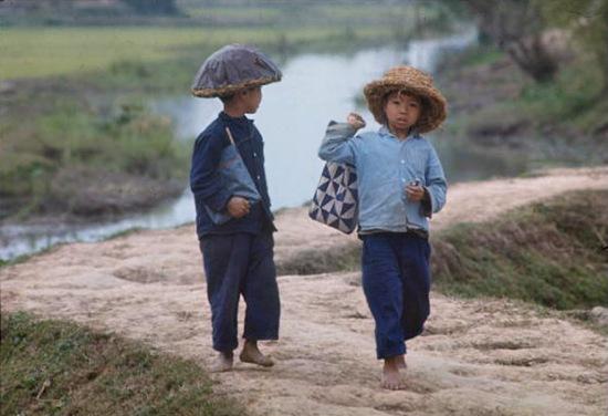1967. Trẻ em miền Bắc chân đất đi học, đội mũ rơm chống mảnh bom.