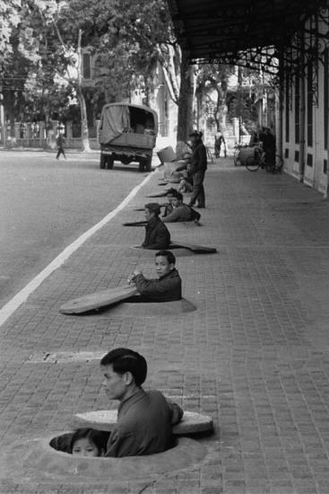 1967. Cư dân Hà Nội ngồi trong hố trú bom cá nhân đợi còi báo hiệu chấm dứt không kích.