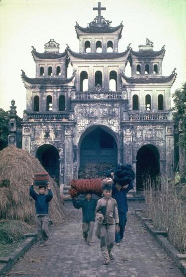 1967. Phía trước một nhà thờ ở Phát Diệm, người lao động khiêng sợi gai dầu dùng để dệt thảm và chiếu.