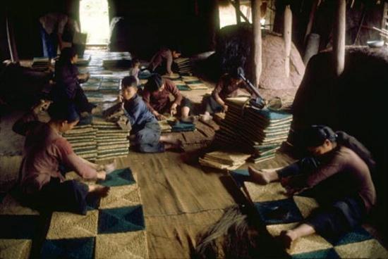 Thợ dùng cối xay thô sơ để nghiền những quả dâu dùng nhuộm sợi gai dầu.