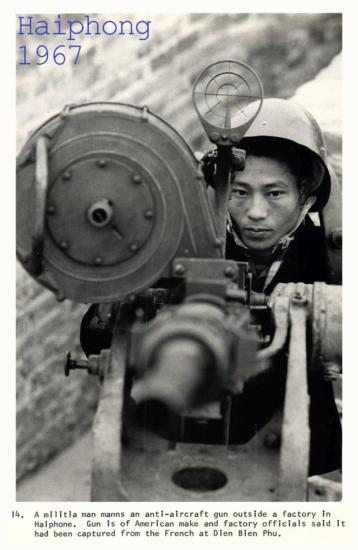 1967. Một dân quân điều khiển khẩu súng phòng không bên ngoài một nhà máy tại Hải Phòng. Khẩu súng này do Mỹ chế tạo và tịch thu được từ người Pháp tại Điện Biên Phủ.