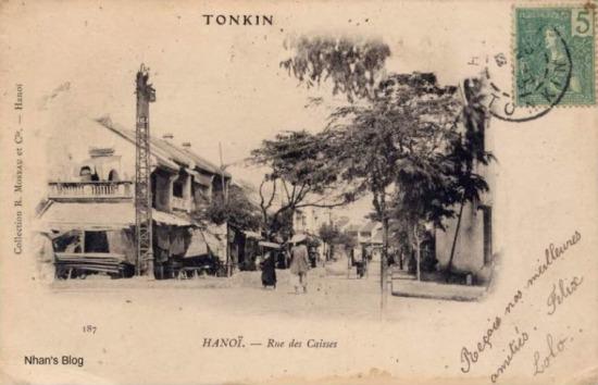 Phố Hàng Hòm nhìn từ điểm giao cắt với phố Hàng Gai - Hàng Bông. Cũng như nhiều bức ảnh xưa, các bức bưu thiếp này cho thấy có một thời trên các phố Hà Nội có hai loại cột điện: loại cột truyền tải, một loại cột đèn chiếu sáng