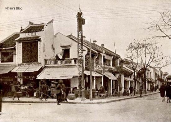 Ngôi nhà góc phố, nơi một người đàn ông đang cúi nhìn xuống phố từ hàng lan can tầng 2, là ngôi nhà đầu tiên của phố Hàng Bông bên dãy số chẵn (số 2). Cạnh đó là một cơ sở thờ tự (của người Hoa?)