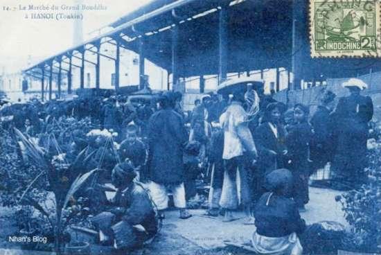Khu vực bán cây hoa cảnh thu hút các bà đầm. Trong ảnh ta có thể nhận thấy một phần của nhà máy sợi Bourgouin Meiffre (nhà máy sợi Bắc Qua), được xây dựng năm 1891 ở sau chợ Đồng Xuân.