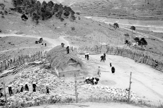 010-1950 Aerial view of people constructing building in fortified town-