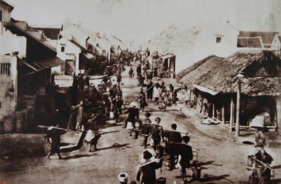 Phố Hàng Mắm với đoàn người gánh các thùng gỗ đựng mắm từ bến sông vào các cửa hàng.