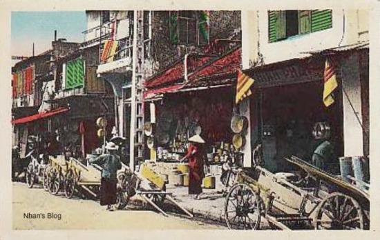 Phố Hàng Thiếc trong ngày lễ. Phố xá treo lá cờ ba sọc đỏ trên nền vàng. Theo Wikipedia:  lá cờ này được dùng từ năm 1890 đến 1920, trước khi Khải Định quyết định thay đổi cờ.