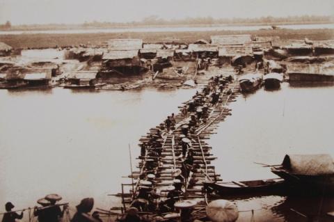 028.Lúc này, cầu Long Biên bắc qua sông Hồng chưa hình thành. Ảnh của Rousseau cho thấy vai trò của giao thông đường thủy bằng thuyền gỗ, bè mảng truyền thống hay các loại tàu chạy máy hơi nước. Mùa cạn, những cây cầu phao này sẽ thay thế.