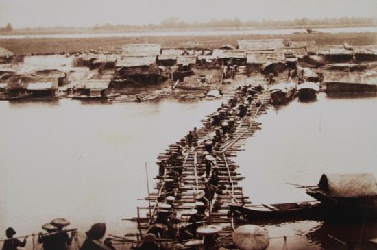 Lúc này, cầu Long Biên bắc qua sông Hồng chưa hình thành. Ảnh của Rousseau cho thấy vai trò của giao thông đường thủy bằng thuyền gỗ, bè mảng truyền thống hay các loại tàu chạy máy hơi nước. Mùa cạn, những cây cầu phao này sẽ thay thế.