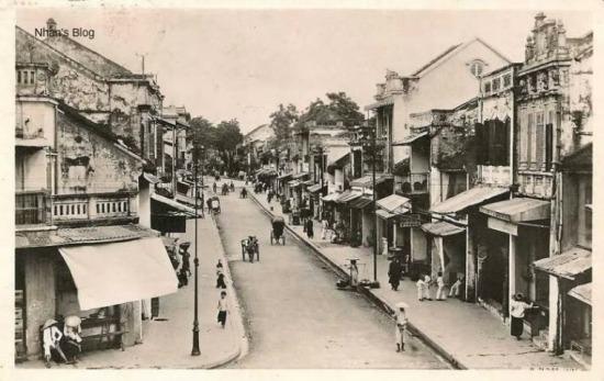 Phố Hàng Hòm nhìn từ điểm giao cắt với phố Hàng Quạt - Hàng Nón. Quán nước nơi hai người đàn ông đội nón ngồi ngóng ra phố là ngôi nhà cuối