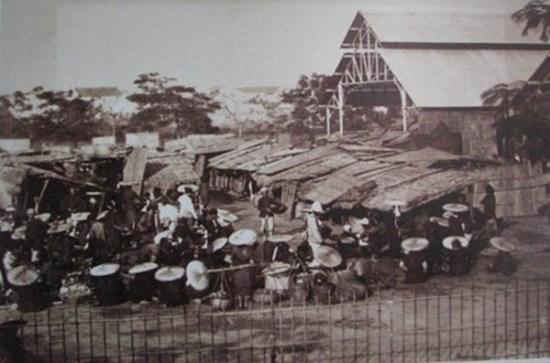 001.Chợ ở Hà Nội. Bên cạnh các gian hàng tranh tre nứa lá đã có khu nhà lớn mái tôn do người Pháp xây dựng.