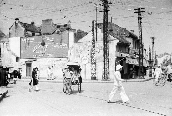 HANOI 1940 - Góc Phố Hàng Gai - Hàng Đào, Hàng Gai bên trái hình đường tàu điện từ Bờ Hồ rẽ trái theo phố Hàng Gai, Hàng Bông - Cửa Nam đi Hà Đông.  Bờ Hồ - Hàng Đào - Hàng Ngang đi Đồng Xuân, Quán Thánh - Bưởi Trong hình là nơi giao nhau hai tuyến xe điện trước khi vào ga Bờ Hồ