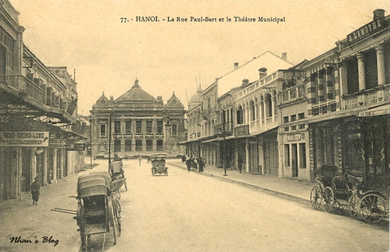 Toàn cảnh đoạn đầu phố Tràng Tiền. Xe hơi thời kì đầu. Cửa hàng cạnh phải ảnh treo biển hãng thời trang ALAMOTHE