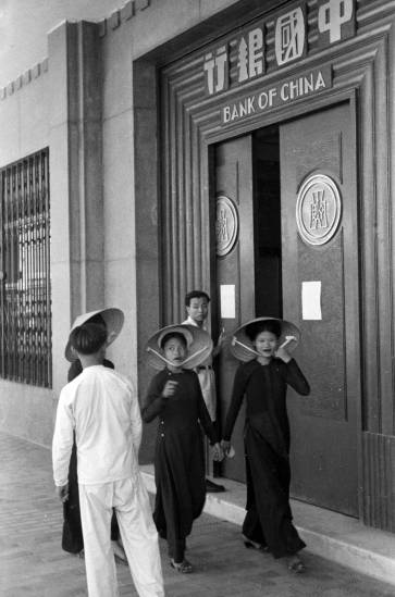1940 - Women in conical hats walking past Bank of China entrance in Hanoi