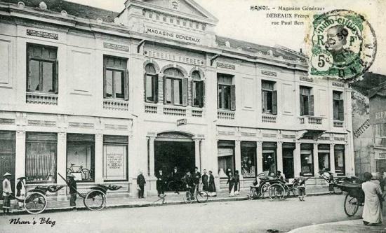 Trực diện Bách hóa Debeaux nhìn từ phố Nguyễn Xí. Trong số các mặt hàng trưng trong các ô cửa có xe đạp đến từ Saint Etienne