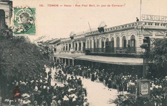 Ngày hội Carnaval. Người Pháp, người Việt cùng chen chân dõi theo đoàn diễu hành. Trên tấm biển ở ban công tầng hai của khách sạn có thể đọc được dòng chữ PIANOS & MUSIQUE.
