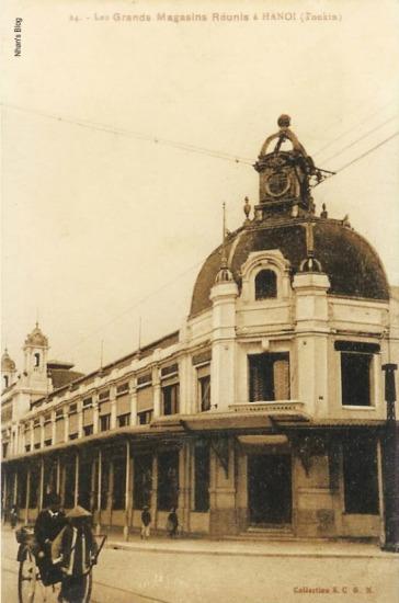 Toàn cảnh nhà Godard phía mặt phố Hàng Bài và Hai Bà Trưng. Đồng hồ trên tháp vẫn chưa được lắp, tuy nhiên hàng cột đỡ mái hiên làm sát ra mép vỉa hè.