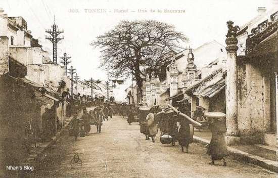 Tiếp nối trình tự không gian. Gần đền Dũng Thọ, số nhà tiếp theo với những trụ cổng đình đền. Đây chính là đình Kim Ngân (số nhà 42), nơi thờ tổ nghề của người gốc làng Châu Khê. Về thời gian, bức ảnh này được chụp trước năm 1906. Chứng cớ là ngoài sự nguyên vẹn của cây cột trái của đền Dũng Thọ, phần đỉnh hàng cột điện khác hoàn toàn so với các các bức ảnh về sau. Có vẻ thời kì đầu hệ thống cột điện thực hiện chức năng truyền tải, về sau chuyển sang chức năng phân phối.