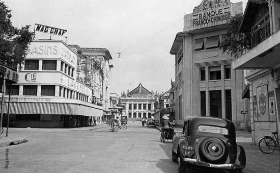 Mép trái bức ảnh thấy rõ trên hàng hiên ngôi nhà trước đây là tiệm ảnh Pierre Dieulefils có biểu tượng Gà Trống Vàng, hình như KS thôn tính tiệm ảnh xưa đeer mở rộng ra sát phố Tràng Tiền? Cửa sổ tầng một hiệu thuốc J. Blanc bị bít đi, nhưng cấu trúc gỗ tầng hai vẫn nguyên vẹn như ban đầu. Nhìn về phía Nhà hát lớn thấy rõ tấm biển Hanoi Hotel (sau 1954 đổi thành KS Dân Chủ)