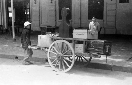 HANOI 1940 - Man moving luggage and cello case with cart