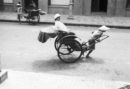 HANOI 1941 - Street scene. Man traveling in a rickshaw
