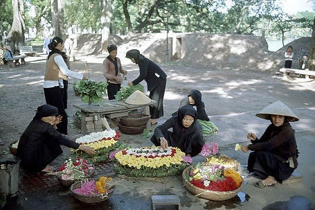 North Vietnam, 1965 during war, paesant women in Hanoi making and selling flower wreaths crouching in the street, other in the background sell vegetables.