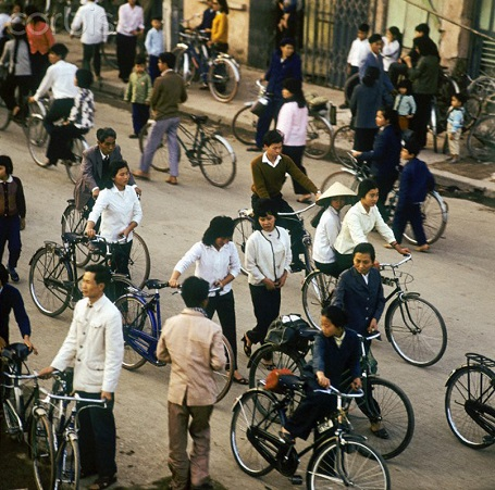 "01 Mar 1973, Hanoi, Vietnam --- Vietnamese people with bicycles in a street in Hanoi in North Vietnam, photographed in March 1973. The United States of America flew about 2,000 air attacks on cities and targets in North Vietnam during the ""Christmas bombings"" in 1972. The peace agreement was signed on the 27th of January in 1973 in Paris. Photo: Werner Schulze --- Image by © Werner Schulze/dpa/Corbis"