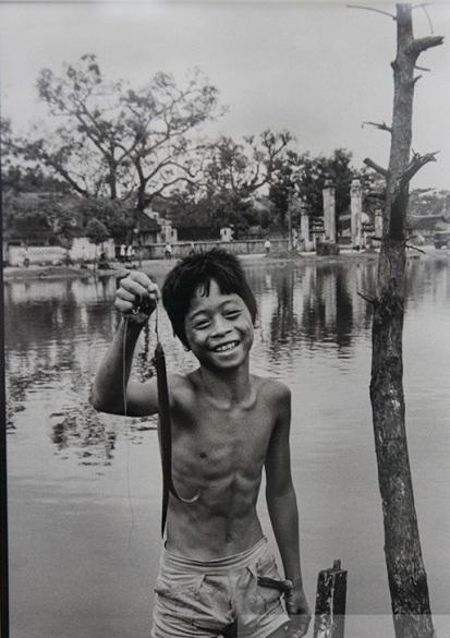 034.Một cậu bé khoe con cá vừa câu được ở hồ Đồng Nhân, nay hay được gọi là hồ Hai Bà.