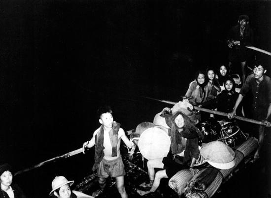 người công giáo bỏ đi khỏi vùng do CS kiểm soát giữa đêm đen nở nụ cười khi thuyền của họ cặp được vào tàu đổ bộ của Pháp mà sẽ đưa họ đến nơi tự do. Khoảng năm 1954.