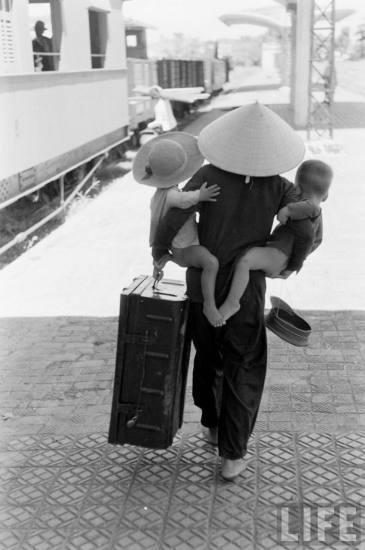 .... mẹ và hai con, tay xách nách mang, trên đường vào miền Nam