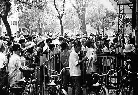 Hàng chục người tập trung ở ngoài một tòa nhà ở Hà Nội để nhận giấy tờ xuất cảnh.