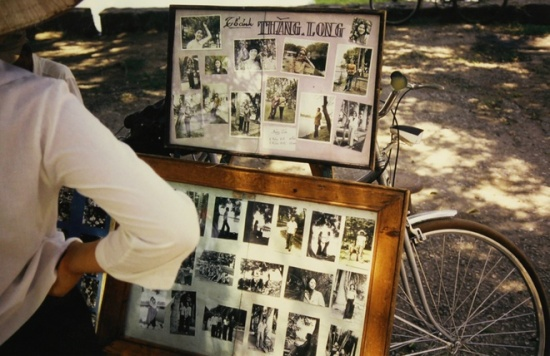 """Michel hay thuê xe đạp đi khắp nơi ở Hà Nội vì thành phố đẹp, có nhiều hồ và công viên. Bức ảnh ghi lại một """"tiệm nhiếp ảnh di động"""" trong công viên Thống Nhất. Kỷ niệm mà ông nhớ nhất khi ấy là nơi ngã tư giao nhau gần công viên ban đêm chỉ có một đèn điện chiếu sáng. """"Có lần, tôi trông thấy hai học sinh ngồi học bài ngay dưới đèn đường. Đó là hình ảnh tôi không bao giờ quên, tiếc là không ghi lại được"""", ông nói."""