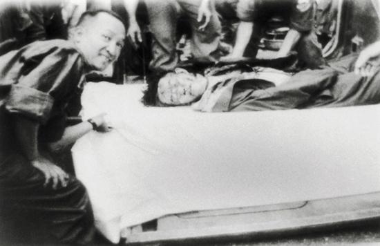 Một sĩ quan thuộc phe đảo chánh, vẻ mặt hớn hở, bên cạnh xác ông Ngô Đình Nhu trước Bộ Tổng Tham Mưu.
