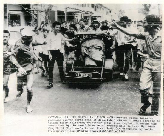 2-11-1963 - Đám đông người Việt hân hoan cười chế nhạo khi xích lô chở đầu bức tượng Hai Bà Trưng bị đập phá đi vòng quanh đường phố Sài Gòn. Tượng đài Hai Bà Trưng đã bị đám đông đập phá vì nó trông giống bà Ngô Đình Nhu. (AP Wirephoto)