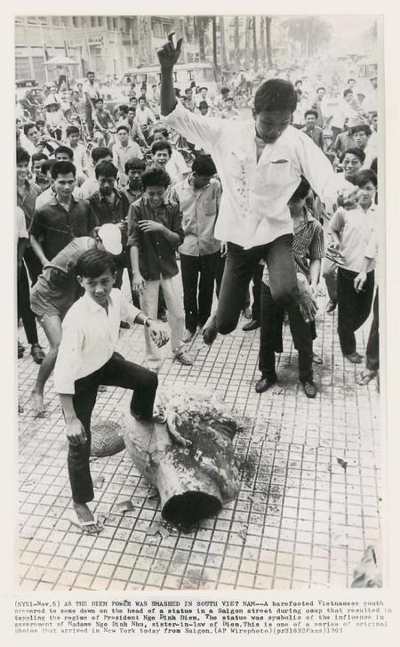 5-11-1963 - Một thanh niên VN chân không giày dép chuẩn bị nhảy xuống trên đầu một bức tượng Hai Bà Trưng trên một con đường ở Sài Gòn.