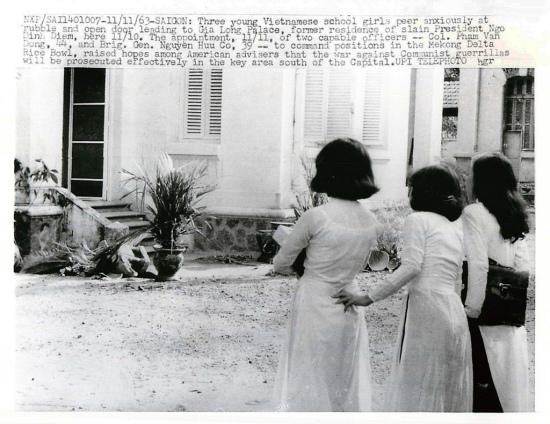 Sài Gòn 10-11-1963 - Ba nữ sinh trẻ VN hiếu kỳ nôn nóng chăm chú nhìn vào đống đổ ngổn ngang và cánh cửa mở dẫn vào dinh Gia Long.