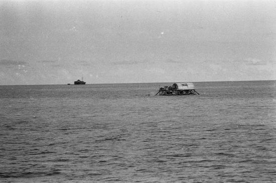 Nhà cao cẳng trên đảo Đá Lát. Cờ Tổ quốc được sơn lên mái tôn như khẳng định chủ quyền của Việt Nam trên đảo này. Xa xa là những gì còn lại của chiếc tàu Tuscany bị bão đánh dạt lên đảo từ năm 1962.