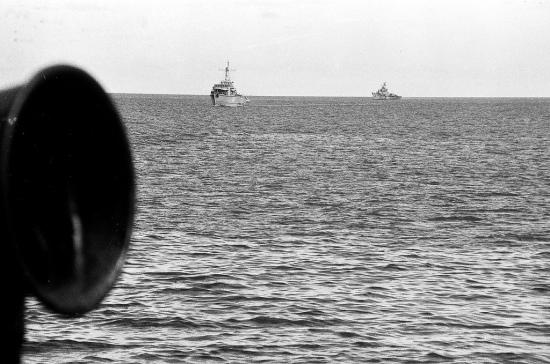 """Chiếc Petya đi theo sau HQ-861 Đá Đông là một trong những đảo chìm của quần đảo Trường Sa. Đảo chìm - Như các bạn thấy trong hình, là một căn nhà Cao cẳng, đứng giữa mênh mông biển cả. Đây là một phần đá san hô có thể nhô lên khỏi mặt nước khoảng 50, 60 cm mỗi khi nước biển rút xuống. Những người lính sống ở đảo chìm cả ngày quanh quẩn trong vài chục mét vuông nhà. Khi triều xuống, họ cũng có thể xuống """" dạo chơi"""" vài bước. Mỗi đảo, thường nuôi rất nhiều c hó. Những người lính đảo rất quý các chú khuyển này và coi chúng như những người bạn thân thiết. Đảo Đá Đông. tháng 5/1988. (NVT)"""
