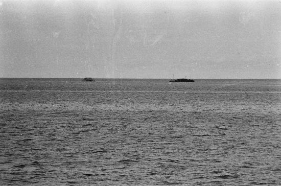 """Trong ảnh trên bên cạnh nhà cao cẳng là một pông tông, Có thể đó là chiếc pôngtông DL10 """"Hồi đó ra đảo chúng tôi thường ở một tăng (18 tháng), có người ở hai tăng mới được về phép. Còn tôi trải qua bốn cái tết liên tục ngoài đảo, từ lúc là trung úy (năm 1988) cho tới khi về bờ (năm 1991) thì sắp lên đại úy. Cả năm trời không có tàu ra thăm"""" - trung tá Phạm Hùng Vĩ, khi ấy là trưởng pôngtông (một loại sà lan được neo cạnh các bãi san hô) chốt giữ đảo Đá Đông từ tháng 8-1988, kể. Thứ kết nối duy nhất với đất liền là đài Vec 206 của Liên Xô buộc vào ăngten cột trên """"sân thượng"""" pôngtông. Pin hết lại trút ra, đổ nước muối vào phơi nắng đến tối rồi nghe tiếp. Trước tết năm 1989 nửa tháng, pôngtông DL10 mới có tàu ra cấp một con heo và ít kẹo, mứt ăn tết sớm. Giao thừa, anh em quây quần bên chiếc đài Vec nghe Chủ tịch nước chúc tết. Nhưng sóng yếu quá, nghe tiếng được tiếng mất. Rồi mọi người thi nhau kể chuyện về quê hương mình, gia đình mình, cả những ước mơ và cùng nhau phá lên cười. Anh Vĩ nhớ lại những giây phút buồn nhất và cũng lãng mạn nhất: """"Cứ trời quang là anh em lên nóc pôngtông ngó qua đảo Trường Sa Đông. Tôi ngồi nhìn về hướng bắc, cố hình dung xa xa tận đường chân trời đó là đất liền. Bao nhiêu nỗi nhớ dành hết cho nhà, cho lũy tre, cho làng xóm, cho hình ảnh những người nông dân trên bờ đê đường làng..."""". Mỗi lần tàu ra chỉ cập đảo mấy tiếng, viết thư không kịp. Anh em buồn quá, nhớ nhà quá cứ viết sẵn thư nhưng không được đề ngày. Phần tái bút nhiều khi dài gấp mấy lần phần thư vì trong thời gian chờ tàu ra lâu quá. Có người gửi một lúc 12 lá thư. Hồi ấy không có phong bì. Tem thư thì hiếm lắm. Bộ đội tự làm phong bì. Tem thì dặn người nào thân thân: """"Nhớ dán giúp cái tem, tôi cho ông ốc nón, cá khô"""". """"Có người anh em, bố mẹ mất nhưng phải gần năm sau mới nhận được thư người nhà báo"""" - anh Vĩ khẽ lắc đầu khi nhớ lại quãng thời gian quá nhiều gian khổ ấy. Người chỉ huy ngày ấy chùng giọng khi kể về cô em gái mất hồi tháng 1-1990 nhưng đến cuối năm 1991 anh"""