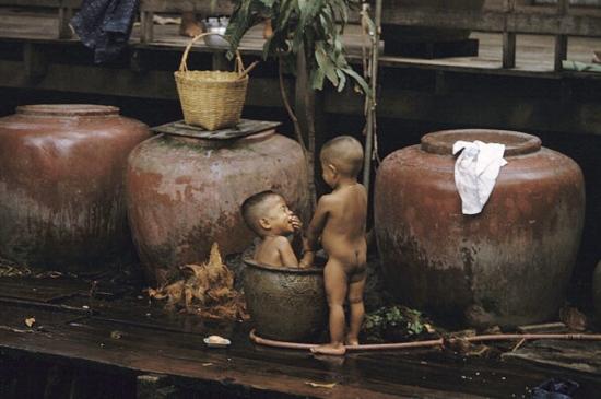 Hai cậu bé vui đùa trong khi tắm bên một con đường ở Chợ Lớn.