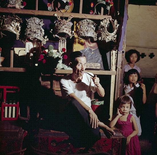 Ông bố người Hoa hút thuốc bằng tẩu bên 3 đứa con gái tại cửa hàng bán trang phục sân khấu của mình ở Chợ Lớn năm 1961.
