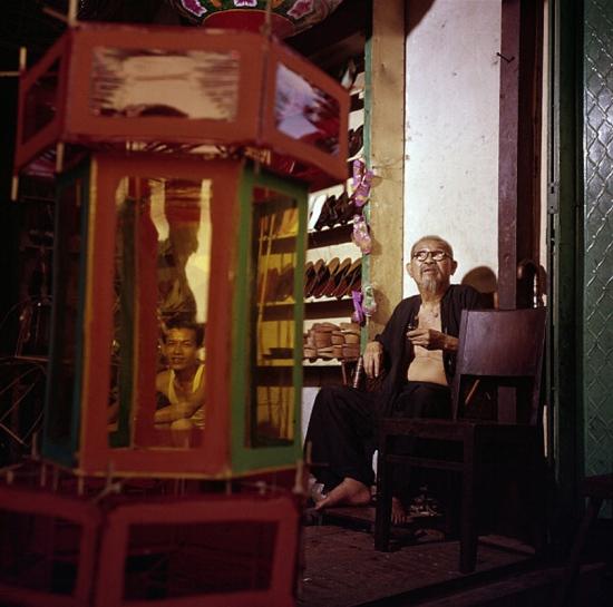 Một thợ đóng giày cao tuổi ngồi trong cửa hàng giày của mình, bên cạnh là một kệ trưng bày giày dép.