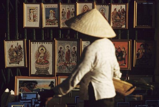 Một người phụ nữ đội nón lá đi qua cảnh xửa xếp treo đầy tranh ảnh tôn giáo của người Hoa ở Chợ Lớn.