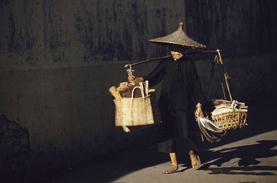Cụ bà người Hoa với gánh hàng bàn chải, chổi và quạt trên vai.